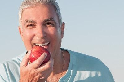 Man eating apple with partial dentures in Missoula MT