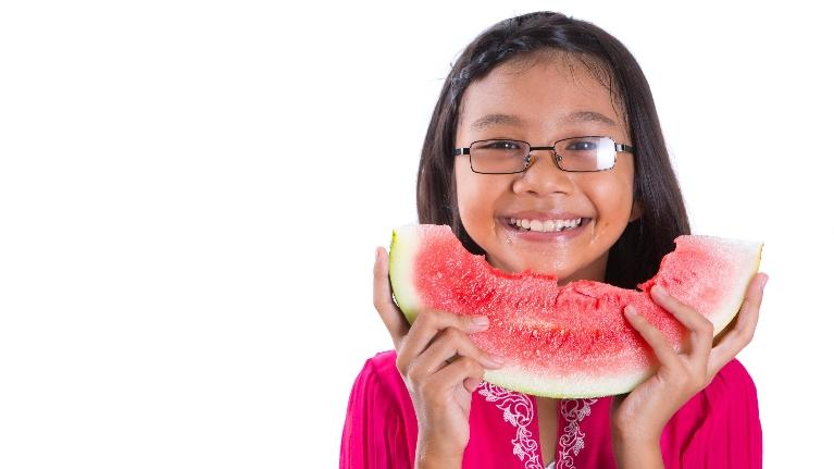 Young Girl Smiling, Holding Watermelon | Dentistry in Missoula
